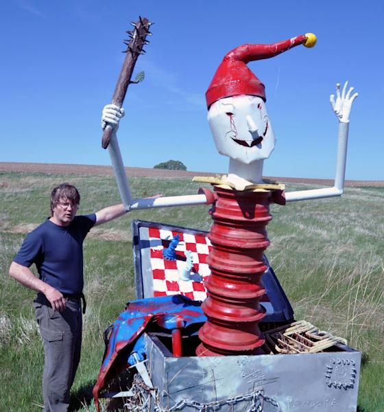 In this May 10, 2012 photo, Wayne Porter explains the concept behind a spiked mallet wielding Jack jumping out of Pandora's Box, one of the more than 40 works of art at his Porter Sculpture Park, in Montrose, S.D. (AP Photo/Dirk Lammers)