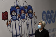 """A woman wearing a face mask to help curb the spread of the coronavirus walks by a billboard depicting medical workers flight against the COVID-19 bearing the words """"Wear Face Mask"""" on display along a hutong alley in Beijing, Thursday, Oct. 14, 2021. (AP Photo/Andy Wong)"""