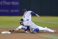 Houston Astros shortstop Carlos Correa, top, tags out Oakland Athletics' Seth Brown who was trying to steal second base during the sixth inning of a baseball game in Oakland, Calif., Friday, Sept. 24, 2021. (AP Photo/Jeff Chiu)