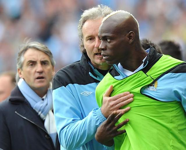 Manchester City's Italian striker Mario Balotelli (R) is restrained as Joey Barton (not pictured) leaves the field during the English Premier League football match between Manchester City and Queens Park Rangers at The Etihad stadium in Manchester, north-west England on May 13, 2012. AFP PHOTO/PAUL ELLIS RESTRICTED TO EDITORIAL USE. No use with unauthorized audio, video, data, fixture lists, club/league logos or 'live' services. Online in-match use limited to 45 images, no video emulation. No use in betting, games or single club/league/player publications.PAUL ELLIS/AFP/GettyImages