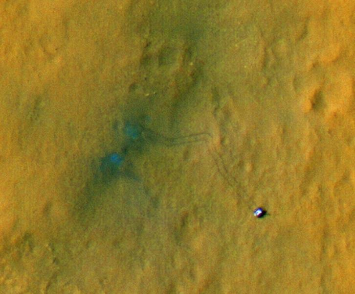 TO PROVIDE AND ALTERNATE CROP - This handout image provided by NASA/JPL-Caltech/Univ. of Arizona, shows tracks from the first drives of NASA's Curiosity rover are visible in this image captured by the High-Resolution Imaging Science Experiment (HiRISE) camera on NASA's Mars Reconnaissance Orbiter. The rover is seen where the tracks end. The image's color has been enhanced to show the surface details better. The two marks seen near the site where the rover landed formed when reddish surface dust was blown away by the rover's descent stage, revealing darker basaltic sands underneath. Similarly, the tracks appear darker where the rover's wheels disturbed the top layer of dust. (AP Photo/NASA/JPL-Caltech/Univ. of Arizona) Observing the tracks over time will provide information on how the surface changes as dust is deposited and eroded.