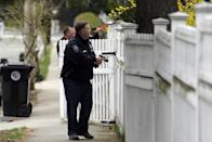 A police officer with is weapon drawn conducts a search for a suspect in the Boston Marathon bombings, Friday, April 19, 2013, in Watertown, Mass. The two suspects in the Boston Marathon bombing killed an MIT police officer and hurled explosives at police in a car chase and gun battle overnight that left one of them dead and his brother on the loose, authorities said Friday as thousands of officers swarmed the streets in a manhunt that all but paralyzed the Boston area. (AP Photo/Matt Rourke)