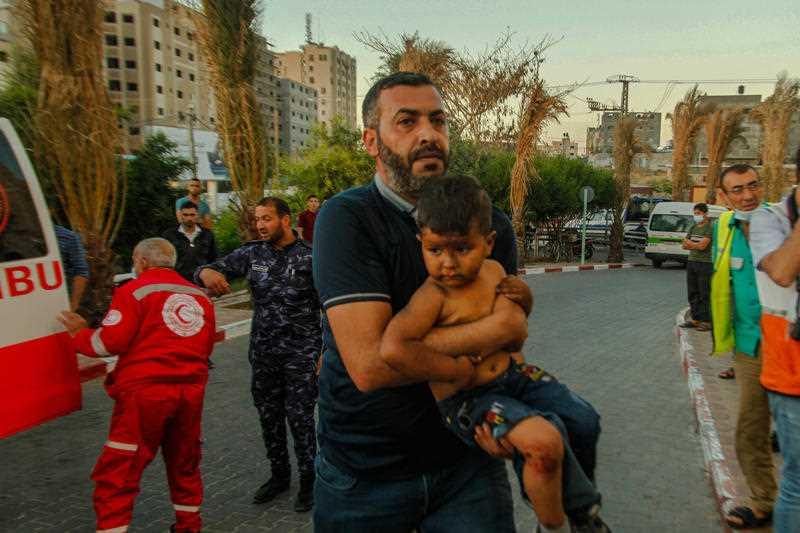 A man is seen carrying a child in his arms in Beit Lahiya, Gaza.
