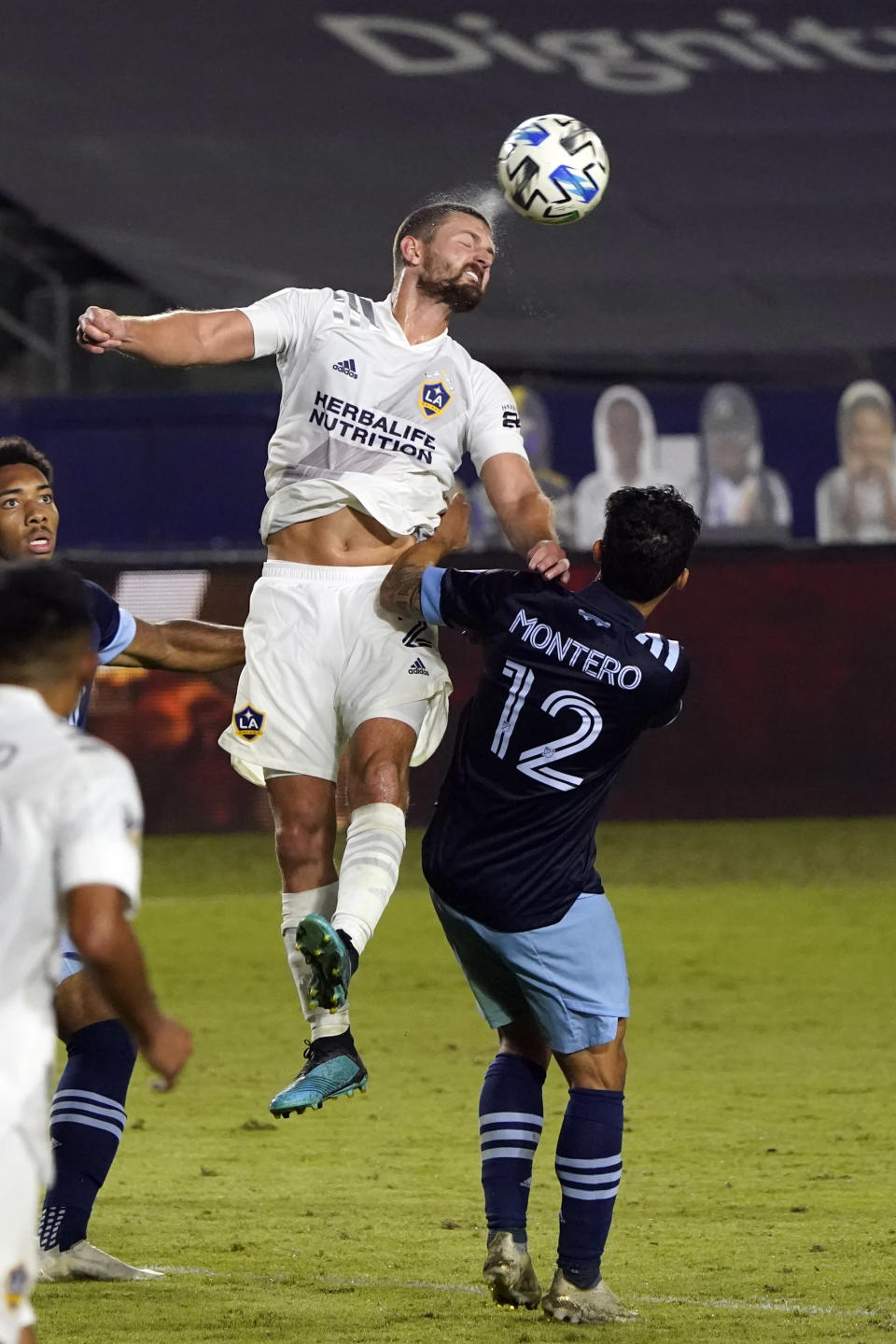 Los Angeles Galaxy's Perry Kitchen, top, heads the ball over Vancouver Whitecaps's Fredy Montero (12) during the second half of an MLS soccer match, Sunday, Oct. 18, 2020, in Carson, Calif. (AP Photo/Marcio Jose Sanchez)