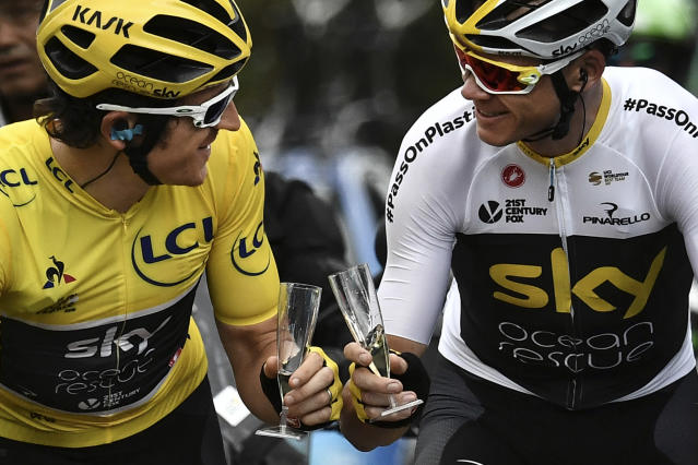 Britain's Geraint Thomas, left, wearing the overall leader's yellow jersey and Britain's Christopher Froome toast with Champagne during the 21st and last stage of the 105th edition of the Tour de France cycling race between Houilles and Paris Champs-Elysees, Sunday, July 29, 2018. (Marco Bertorello, Pool via AP)