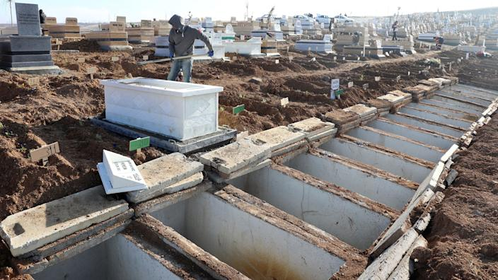 A man backfills a grave in a cemetary alongside more than a dozen other dug gravesites.