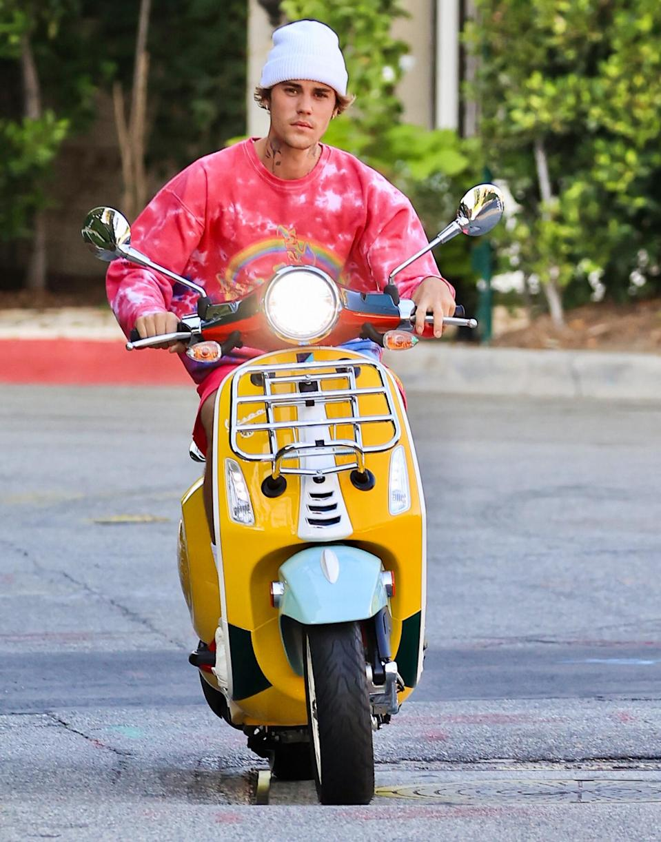 <p>Justin Bieber enjoys a ride around Beverly Hills on his yellow scooter on Monday.</p>