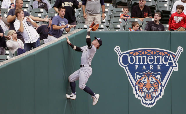 New York Yankees left fielder Clint Frazier climbs up the left field corner to catch a foul fly ball hit by Detroit Tigers' Jake Rogers during the eighth inning of the first game of a baseball doubleheader, Thursday, Sept. 12, 2019, in Detroit. (AP Photo/Duane Burleson)