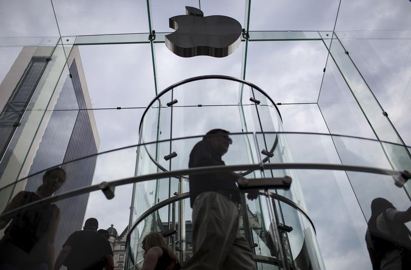 Customers enter the Apple store on 5th Avenue beneath an Apple logo in the Manhattan borough of New York City