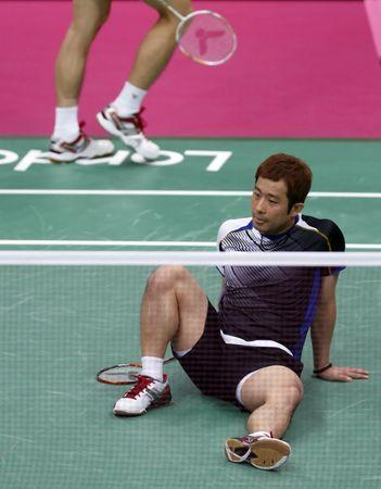 South Korea's Chung Jae-sung sits on the court in disappointment after he and teammate Lee Yong-dae (back) lost their men's doubles badminton semifinal match against Denmark's Mathias Boe and Carsten Mogensen at the London 2012 Olympic Games at the Wembley Arena August 4, 2012. REUTERS/Bazuki Muhammad