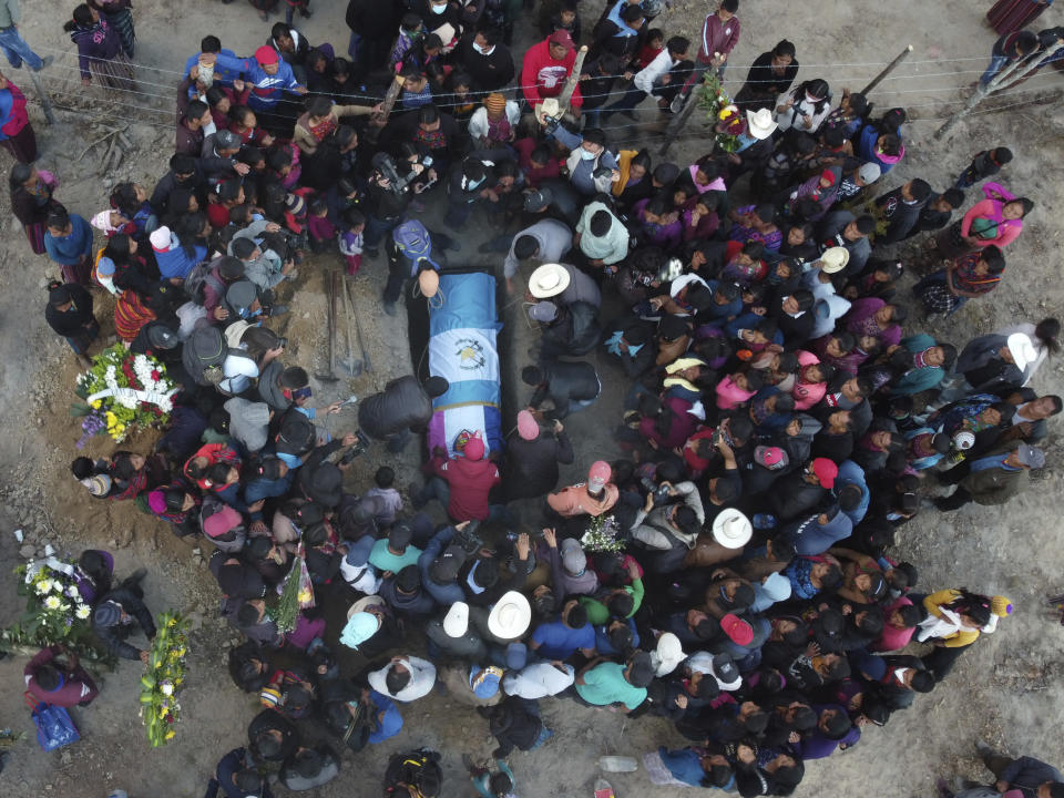 People lower the remains of Elfego Miranda Diaz into a grave, one of the Guatemalan migrants who was killed near the U.S.-Mexico border in January, at a cemetery in Comitancillo, Guatemala, Saturday, March 13, 2021. Thousands of residents of the town gathered Friday night amid tears and applause to receive the remains of 16 of their own, found piled in a charred pickup truck in Camargo, across the Rio Grande from Texas. (AP Photo/Moises Castillo)