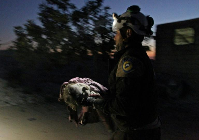 A member of the Syrian Civil Defence (White Helmets) carries a young victim following a reported Russian airstrike on the town of Maaret al-Numan in Syria's northwestern Idlib province (AFP Photo/Abdulaziz KETAZ)