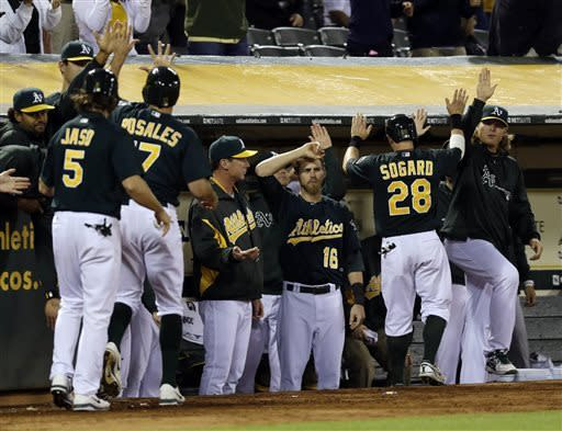 The Oakland Athletics celebrate after a bases-loaded double from Seth Smith during the sixth inning of a baseball game against the Los Angeles Angels on Tuesday, April 30, 2013 in Oakland. Calif. (AP Photo/Marcio Jose Sanchez)