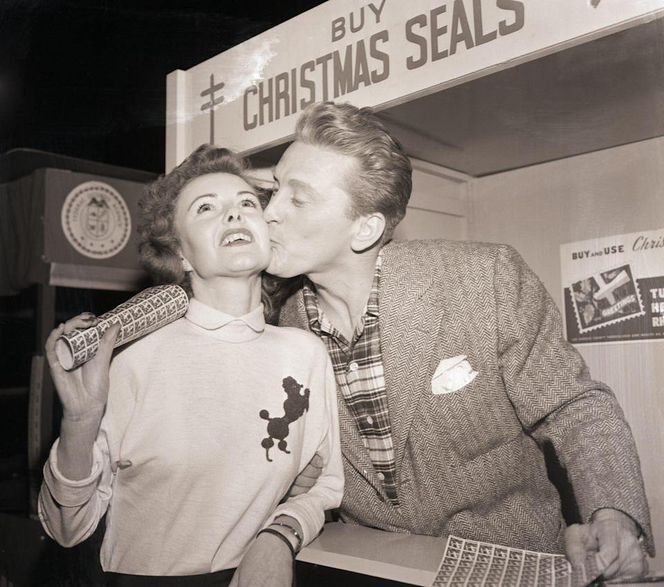<p>A lucky fan is given a kiss by Hollywood hunk Kirk Douglas after buying a roll of Christmas seals from the actor. Back in the '40s, Christmas seals were specially printed stamps for holiday cards and were used to raise money for various charities. </p>