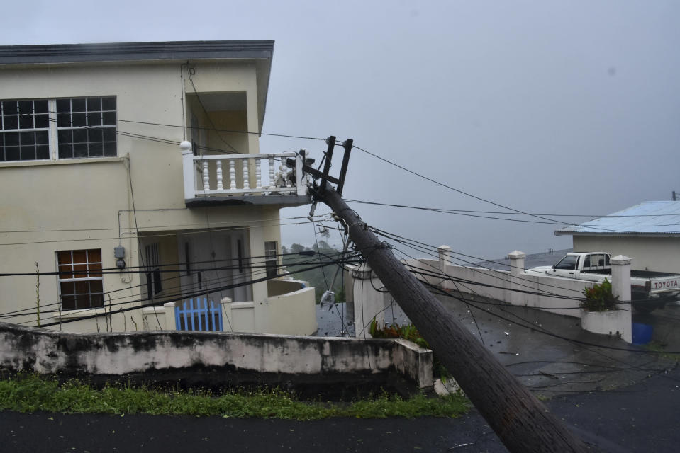 An electrical pole felled by Hurricane Elsa leans on the edge of a residential balcony, in Cedars, St. Vincent, Friday, July 2, 2021. Elsa strengthened into the first hurricane of the Atlantic season on Friday as it blew off roofs and snapped trees in the eastern Caribbean, where officials closed schools, businesses and airports. (AP Photo/Orvil Samuel)