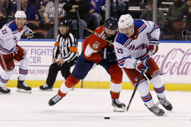 New York Rangers defenseman Adam Fox (23) battles Florida Panthers right wing Brett Connolly (10) for the puck in the second period of an NHL hockey game, Saturday, Nov. 16, 2019, in Sunrise, Fla. (AP Photo/Joe Skipper)