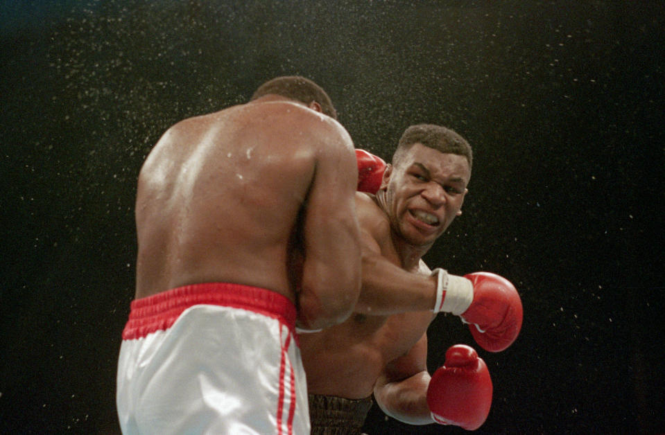 (Original Caption) 1/22/1988-Atlantic City, NJ Ferocious faced Mike Tyson lands the knockout punch to the jaw of challenger Larry Holmes during fourth round of the World Heavyweight Championship.