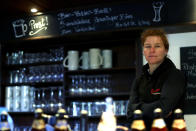 In this photo taken Friday, May 1, 2020 brewery daughter Iris Detter sits at the bar in her 120 year old family brewery and traditional Bavarian restaurant in Altoetting, Germany. The 'Graminger Weissbraeu' brewery, which has been in the same family for a century, is preparing to welcome guests back to its restaurant for the first time in two months — with new rules and fears for the future. (AP Photo/Matthias Schrader)