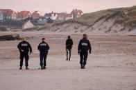 Police officers control migrants as they patrol along the Slack dunes in Wimereux