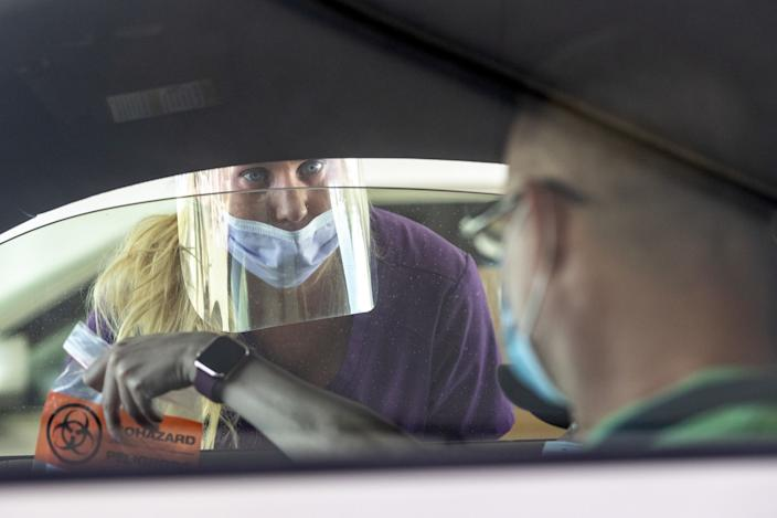 Nurse Debbie Davidson takes a test sample at the COVID-19 testing site at the Kern County Fairgrounds on Thursday.