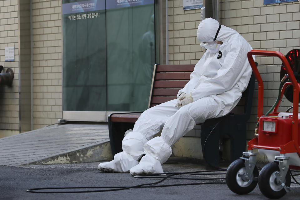 """A member of the medical team takes a rest outside a hospital in Daegu, South Korea, Sunday, Feb. 23, 2020. South Korea's president has put his country on its highest alert for infectious diseases, saying Sunday that officials should take """"unprecedented, powerful"""" steps to fight a viral outbreak. (Im Hwa-young/Yonhap via AP)"""