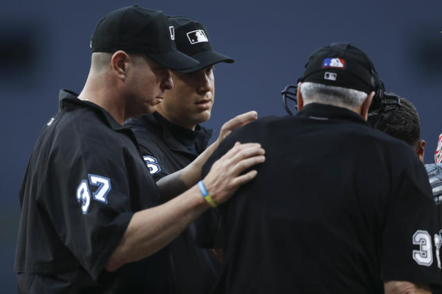 Second base umpire Chris Segal, second from left, and third base umpire Carlos Torres, left, talk with home plate umpire Dana DeMuth after DeMuth was struck by a foul ball during the first inning of a baseball game between the San Diego Padres and the Atlanta Braves, Friday, July 12, 2019, in San Diego. (AP Photo/Gregory Bull)