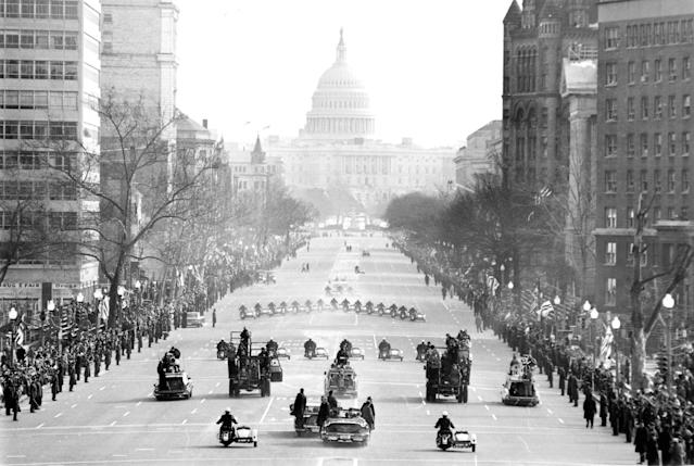 The motorcade bearing President Johnson to the Capitol for his inauguration moves along Pennsylvania Avenue, January 20, 1965. Police on motorcycles lead the way. Johnson is in a closed car at lower center with Secret Service agents on the bumper. Another car full of Secret Service men is close by. (AP Photo)
