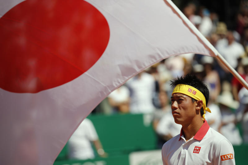 A Japanese flag is seen as Japan's Kei Nishikori prepares to serve against Spain's Rafael Nadal during the men's singles final match of the Monte Carlo Tennis Masters tournament in Monaco, Sunday April 22, 2018. (AP Photo/Christophe Ena)