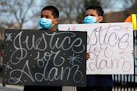 Jacob Perea, 7, left and Juan Perea, 9 holds signs on Tuesday, April 6, 2021, as they attend a press conference following the death of 13-year-old Adam Toledo, who was shot by a Chicago Police officer at about 2 a.m. on March 29 in an alley west of the 2300 block of South Sawyer Avenue near Farragut Career Academy High School.