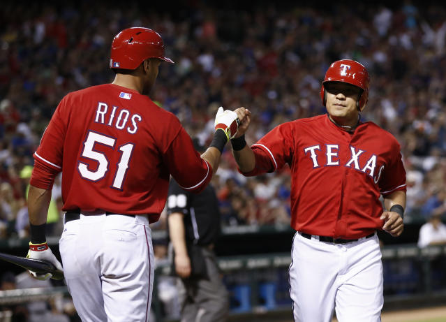 Texas Rangers' Shin-Soo Choo, right, is congratulated by teammate Alex Rios (51) after scoring on a sacrifice fly hit by Prince Fielder against the Boston Red Sox during the fourth inning of a baseball game on Saturday, May 10, 2014, in Arlington, Texas. (AP Photo/Jim Cowsert)