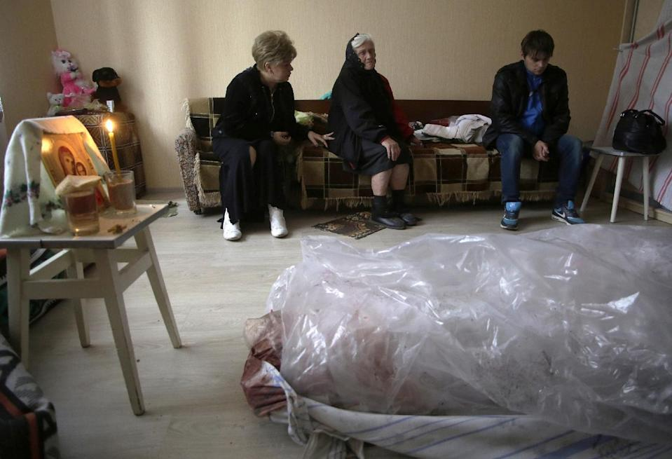 Relatives mourn in Debaltseve behind the body of a woman killed when her building was damaged by rockets during an overnight shelling on September 22, 2014 (AFP Photo/Anatolii Stepanov)