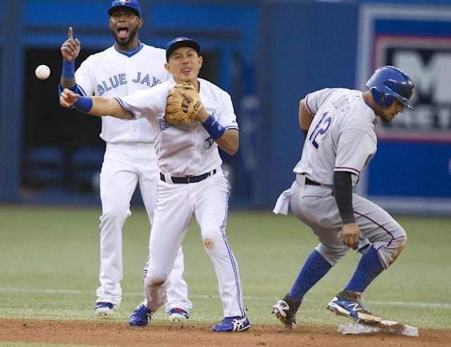 Toronto Blue Jays' Munenori Kawasaki gets the force out at second base on Texas Rangers' Rougned Odor as Blue Jays' Jose Reyes watches during the third inning of a baseball game Friday, July 18, 2014, in Toronto. Geovany Soto was out at first on the double play. (AP Photo/The Canadian Press, Fred Thornhill)