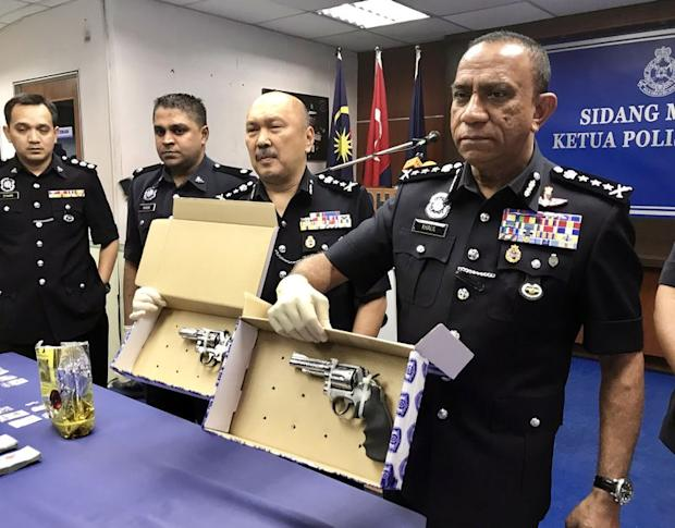 Johor police chief Datuk Mohd Khalil Kader Mohd (far right) with the seized revolvers and drugs at the Johor police contingent headquarters in Johor Baru, February 14, 2018. — Picture by Ben Tan