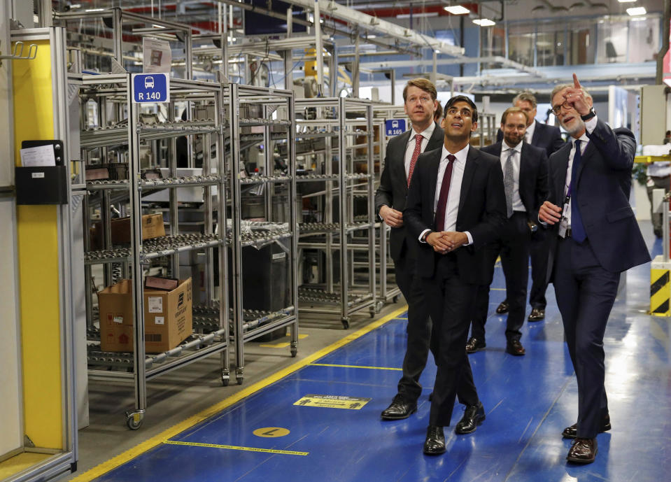 Britain's Chancellor of the Exchequer Rishi Sunak talks with the CEO of Worcester Bosch, Carl Arntzen, right, during a visit to Worcester Bosch factory to promote the initiative, Plan for Jobs, in Worcester, England, Thursday July 9, 2020. (Phil Noble/Pool via AP)