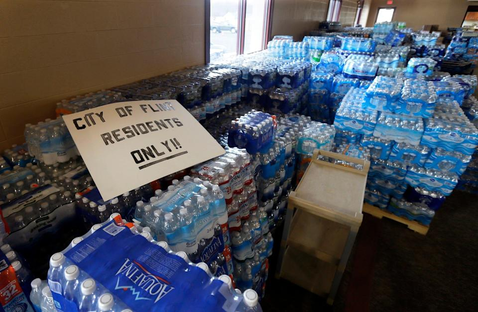 FILE - In this Friday, Feb. 5, 2016 file photo, hundreds of cases of bottled water are stored at a church in Flint, Mich. After months of national attention on lead-tainted drinking water in Flint, many are starting to ask questions about a 74-mile pipeline being built from Lake Huron to the struggling former auto manufacturing powerhouse. The $285 million project is rooted in political ambitions and long-simmering resentment toward Detroit, which for decades had near-total control of the city's water rates. (AP Photo/Carlos Osorio, File)