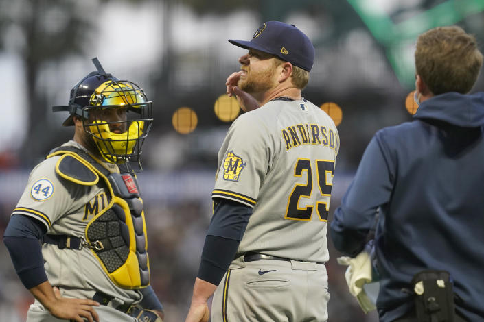 Milwaukee Brewers pitcher Brett Anderson (25) stands next to catcher Omar Narvaez after being struck by the ball on a single by San Francisco Giants' Brandon Crawford during the second inning of a baseball game in San Francisco, Wednesday, Sept. 1, 2021. (AP Photo/Jeff Chiu)