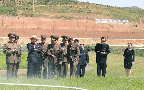 Kim Yo-jong seen on the right during a visit by her brother to a tree nursery in a photo released in 2015 - Credit: AFP PHOTO via Korean Central News Agency