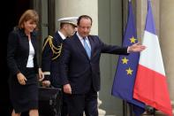 """Anne Lauvergeon (L), head of the commission """"Innovation 2030"""", and French President Francois Hollande leave the Elysee Palace in Paris after the handing of the commission's report, October 11, 2013. REUTERS/Philippe Wojazer (FRANCE - Tags: POLITICS BUSINESS)"""