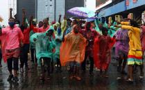 Demonstrators wearing raincoats shout slogans during a protest over alleged police brutality, in Lagos