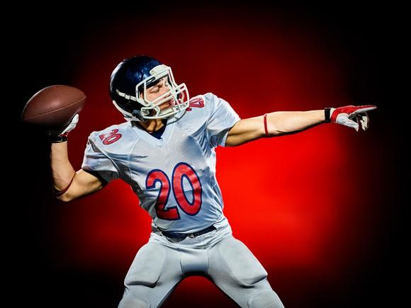 A football player throwing a football.