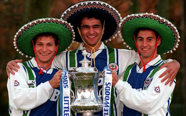 """There will be no shortage of stories to laugh and reminisce over when The Three Amigos, as they fondly became known at Wigan Athletic, reunite at a charity match in May. Twenty-three years have passed since Dave Whelan, Wigan's ambitious owner, sent shockwaves through English football by persuading a trio of Spanish players to join his unfashionable old Third Division club, but the memories remain vivid. The most famous of the group, Roberto Martinez, would go on to win the FA Cup as Wigan manager many years later, an extraordinary triumph the club hope to emulate as they seek to topple Southampton at the DW Stadium on Sunday and, with it, secure a third semi-final trip to Wembley in six seasons. But such a scenario was virtually unthinkable when Martinez pitched up in the Lancashire town alongside the equally unsuspecting Isidro Diaz and Jesus Seba in 1995. Between them they barely spoke a word of English, but while a sceptical wider public and media wondered if Whelan was merely indulging in a PR stunt as he sought to put his team on the map, Wigan embraced the strangers in the same way as they embraced a club, town and way of life that was far removed from what they had known in Spain. Still, their first few weeks were interesting. """"We were playing away somewhere and the three of us turned up in suits and a tie. The problem was the rest of the team were in club tracksuits,"""" Diaz recalled, chuckling away. """"'Ah, f------ hell'. So the next game we turned up in tracksuits but all the other players were wearing suits. 'Oh, we're mistaken again...' Everyone was laughing at us. It was very funny."""" Roberto Martinez in action for Wigan Credit: ALLSPORT After spending the first six months living in the Wrightington Hotel, they moved to a small semi-detached house in Poolstock Lane, just a couple of miles from where Whelan would soon build a new stadium. The problem was the club-sponsored Ford Escort they were given to drive was emblazoned across the side with their nicknam"""