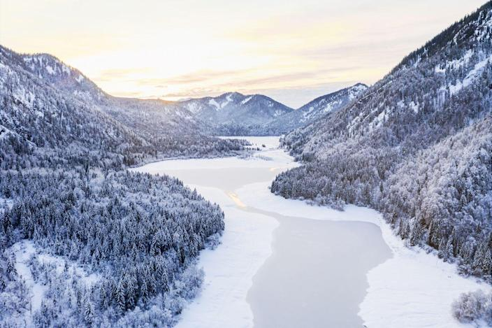 <p>A frozen lake lies in the snow-covered valley of the Chiemgau Alps in Bavaria, Germany.</p>