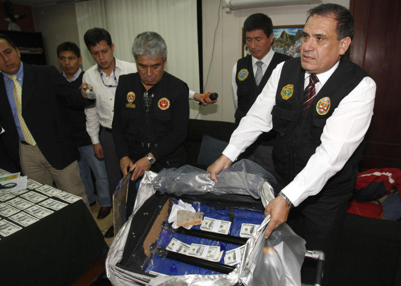 FILE - In this Aug. 17, 2012 file photo, a police officer shows counterfeit $100 U.S. dollar notes during a media presentation in Lima, Peru. The Andean country became more attractive to counterfeiters as Washington's decade-long Plan Colombia program tightened the screws not just on drug traffickers in the neighboring nation but other criminals as well. Counterfeiting in Peru, meanwhile, got better. Counterfeiters earn up to $20,000 in real currency for every $100,000 in false bills they produce after expenses. (AP Photo/Karel Navarro, File)