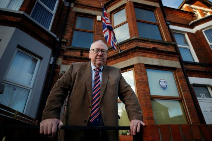 Unionist Orange order leader Gibson poses for a photograph outside his house in Belfast