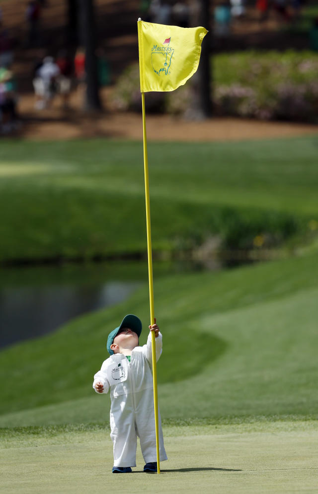 Scott Stallings's son Finn looks at the flag on the fourth green during the par three competition at the Masters golf tournament Wednesday, April 9, 2014, in Augusta, Ga. (AP Photo/Matt Slocum)