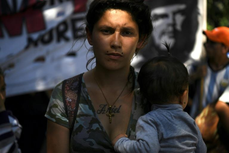 A woman with a baby takes part in a protest outside the Congress building while Argentine Senators discuss an austerity budget in Buenos Aires on November 14, 2018