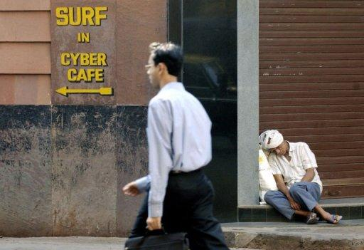 This file photo shows an Indian man passing a Cyber Cafe sign while another one sleeps in a doorway, in Mumbai, in 2004. Global hacking movement Anonymous has called for protesters to take to the streets in 16 cities around India on Saturday over what it considers growing government censorship of the Internet
