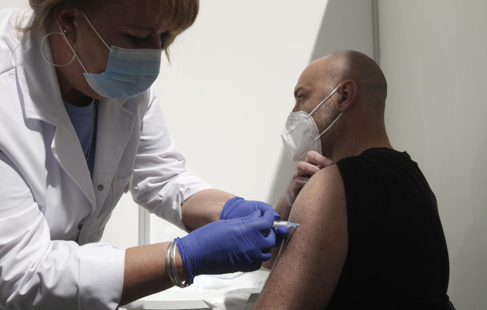 A nurse administers a vaccine to a man at the center for mass vaccination against COVID-19, at A1 Arena in Skopje, North Macedonia, on Monday, April 5, 2021. The tiny Balkan country has begun administrating mass immunization of the army, police and media workers on Monday with about 20,000 doses of Russian Sputnik V donated from neighboring Serbia. (AP Photo/Boris Grdanoski)