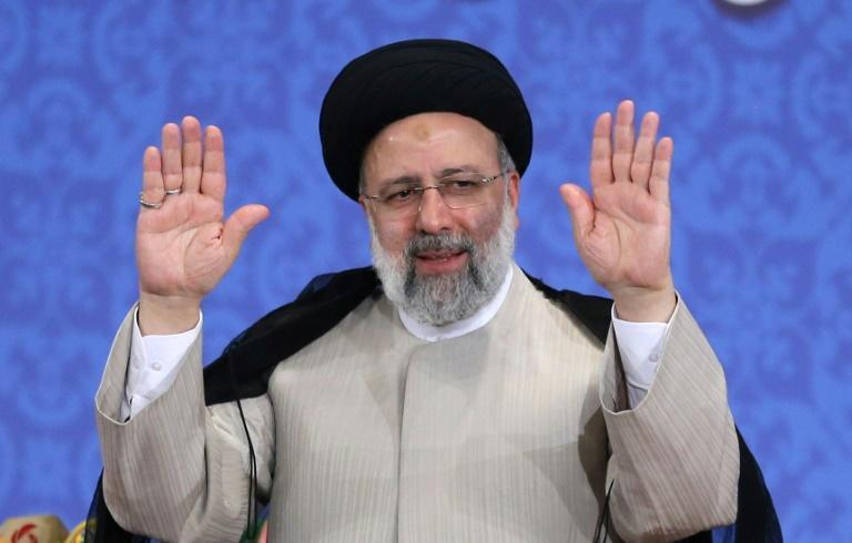 An austere figure from the Shiite Muslim clerical establishment, Raisi smiled and raised his hands as he arrived for his press conference