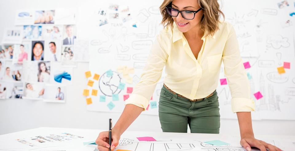 Woman in her 20s drawing a creative business plan at the office.